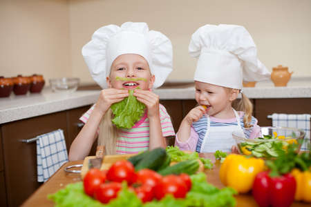 happines: two little girls preparing healthy food and have fun  on kitchen