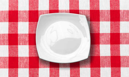 white plate on red checked fabric tablecloth photo