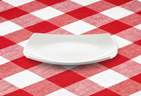 white square empty plate on red gingham tablecloth photo