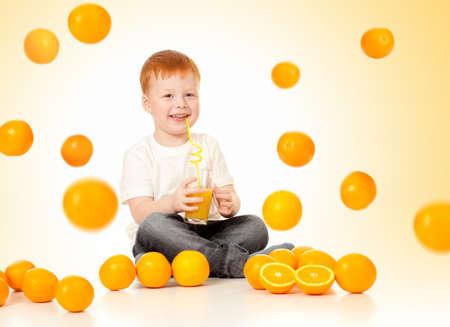 redheaded boy with falling oranges and orange juice photo