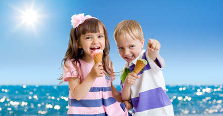 Children with icecream cone outdoor on seashore in hot summer day photo