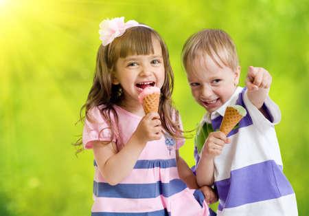 comiendo helado: Los niños con helado de cono al aire libre en días calurosos de verano