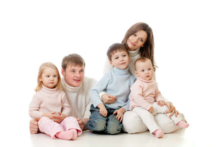 indirectly: happy family sitting on floor and looking sideways on TV with great interest Stock Photo