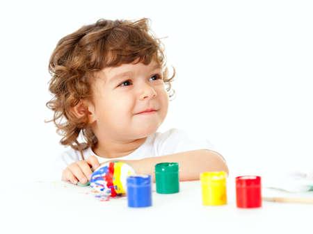 Little curly child painting egg studio shot photo