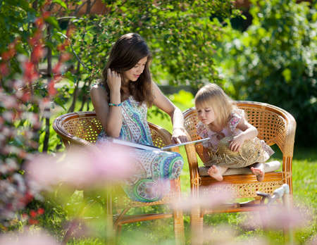 Girls reading book sitting in wicker chairs outdoor in summer day Stock Photo - 11880578