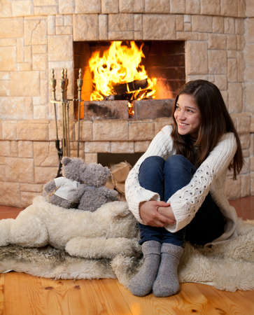 happy teenage girl in winter clothes sitting fireside photo