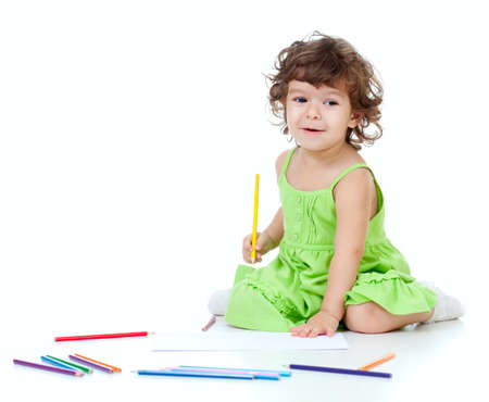 curly headed: Little girl drawing with yellow pencil Stock Photo