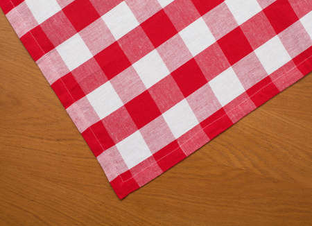 wooden kitchen table with red gingham tablecloth photo