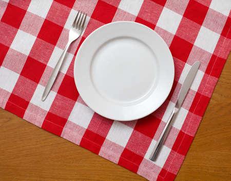 kontrolovány: Nůž, bílý talíř a vidlička na dřevěný stůl s červenou zkontrolovat ubrus