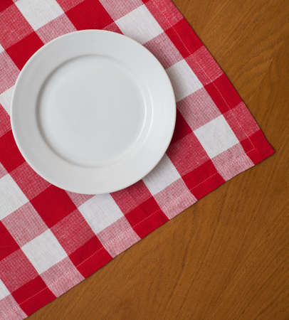 plate setting: white plate on wooden table with red gingham tablecloth
