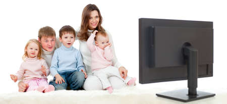 happy family sitting on floor and watching TV or monitor with great interest photo