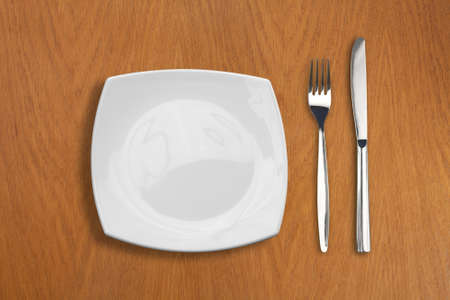 crockery: square white plate, knife and fork on wooden table Stock Photo