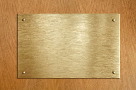 Wooden plaque with gold or brass plate photo