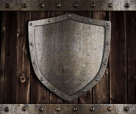 aged metal shield on wooden medieval gates Stock Photo - 12201982
