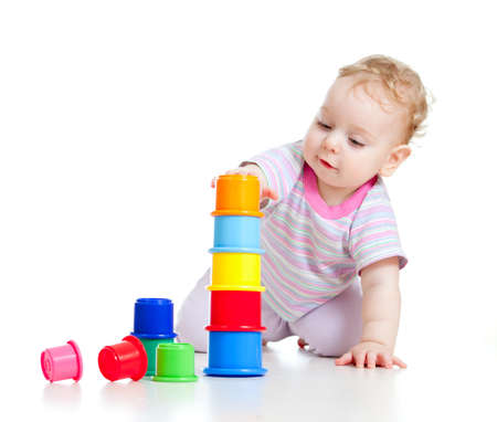 kindergarten toys: Cute little boy building tower from colorful cups isolated on white