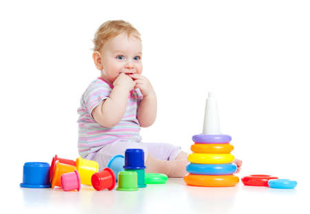 Cute little boy playing colorful toys isolated on white photo
