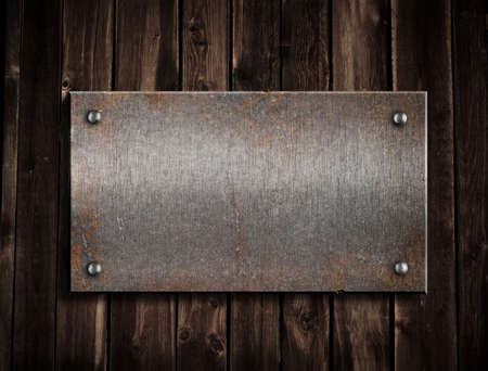 rusty metal plate on wooden background photo