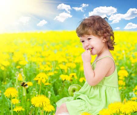 petite fille avec robe: Bébé fille assise au milieu de pissenlit avec des aliments sains de pomme dans ses mains