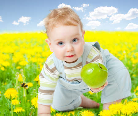 field and sky: Baby boy among dandelion with healthy food apple in his hand