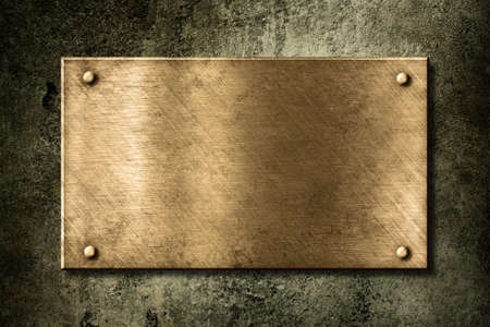 plaque: old golden or bronze plate on wall Stock Photo