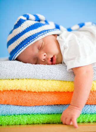 Sleeping baby on colorful towels stack photo