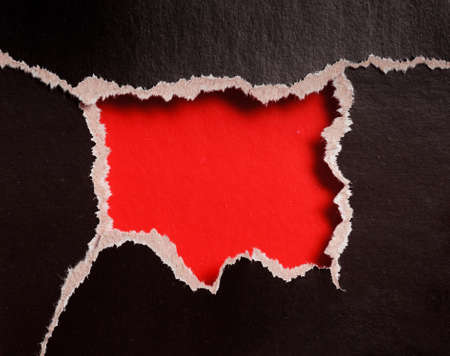torn edges: red hole with torn edges in black paper Stock Photo