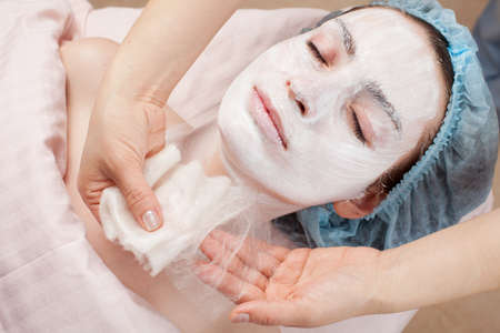 woman face cream: Silk mask applying, beauty treatment young woman face at salon Stock Photo
