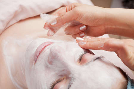 satisfying: Silk mask applying, beauty treatment young woman face at salon Stock Photo