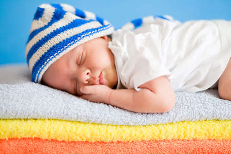 Sleeping newborn baby on colorful towels stack Stock Photo - 12784082