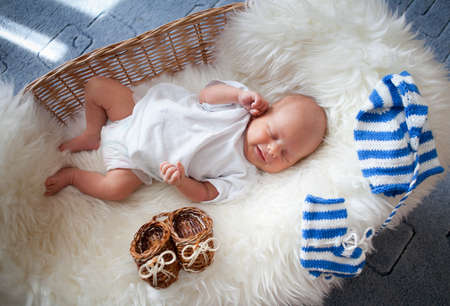 Sleeping newborn baby in wicker basket lying on sheepskin photo