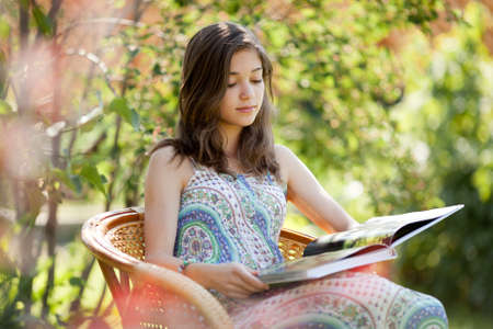 Girl reading book sitting in wicker chair outdoor in summer day photo