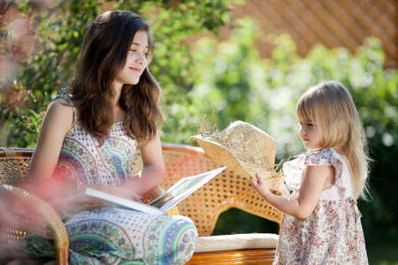Girls reading book sitting in wicker chairs outdoor in summer day Stock Photo - 12784210