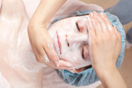 Beautiful woman with facial mask getting beauty treatment at salon photo