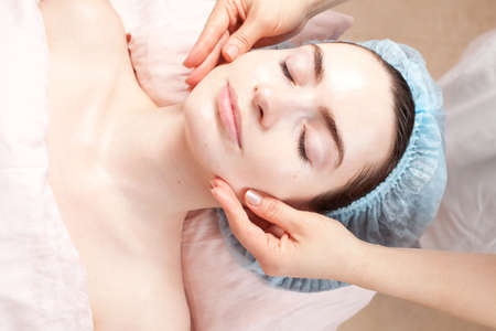 Beautiful woman with clear skin getting beauty treatment - massage of her face at salon photo