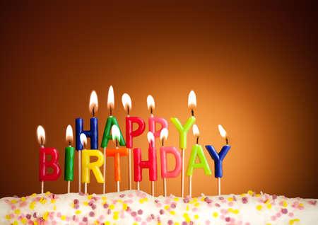 happy birthday cake: Feliz cumplea�os encendieron velas en el fondo de color marr�n