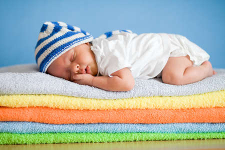 newborn baby: Sleeping newborn baby on colorful towels stack Stock Photo