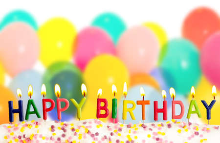 birthday cakes: Happy birthday lit candles on colorful balloons background Stock Photo