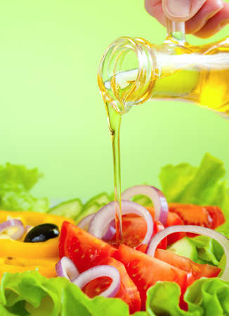 olive oil stream and healthy fresh vegetable salad photo