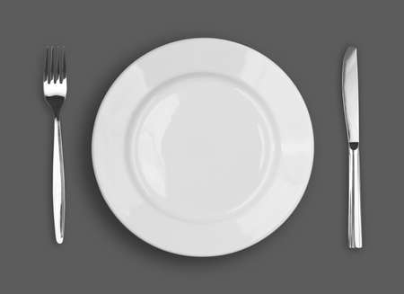 dinner dish: Knife, white plate and fork on gray background Stock Photo