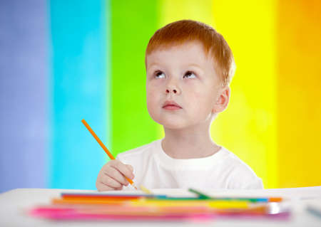 Redheaded adorable boy drawing with yellow pencil on rainbow background photo