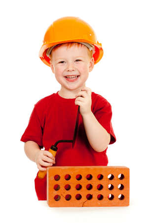 Builder boy or kid in red tshirt and hard hat. Construction concept. photo