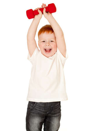 kids club: Red-haired adorable boy making exercise with dump-bells isolated