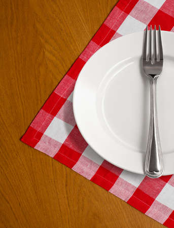 white plate and fork on wooden table with red checked tablecloth photo