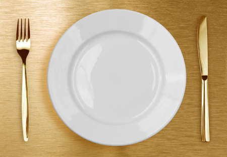 Golden knife, fork and white plate photo