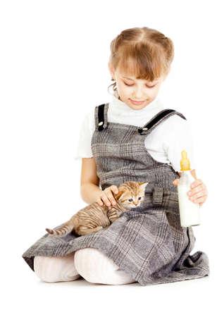 Girl feeding British kitten isolated on white photo