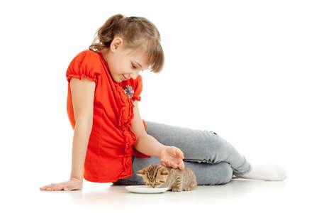 Girl feeding homeless alley cat photo