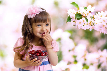 little girl with cherry berries bowl in garden photo