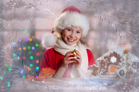 girl in Santas hat with decoration ball in hands photo