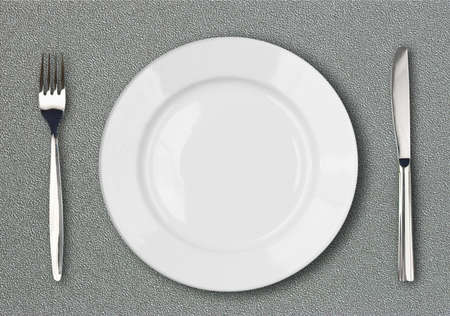 plate setting: White plate, fork and knife top view on gray plastic textured table surface