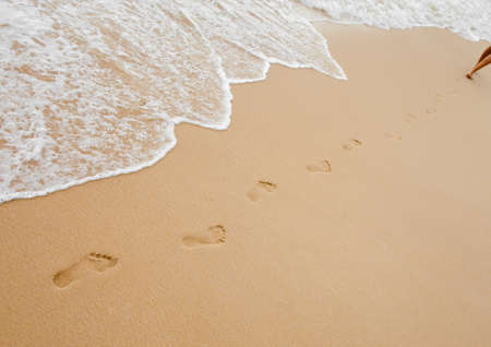 Footprints chain on sand of sea beach photo